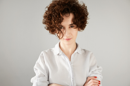 reproach: Close up portrait of outraged young brunette woman with short curly hair cut standing with arms crossed, looking in reproach or mistrust at the camera. Negative face expressions and emotions