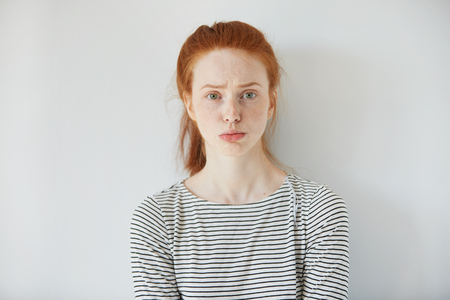 face expressions: Closeup portrait of grumpy or annoyed young woman with red hair wearing striped top, looking at the camera with sad or unhappy expression on her face while having some problem at work. Body language