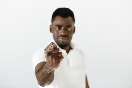 outrage: Close up portrait of angry or annoyed black man making fig gesture showing you are going to get zero nothing. Negative emotions, facial expressions, feelings, body language, signs. Selective focus Stock Photo
