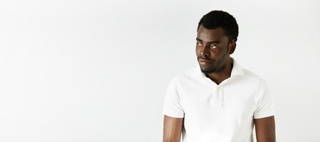 african student: Handsome African American student wearing white polo shirt looking away with sad or disappointed expression, posing against white concrete wall with copy space for your text or advertising content