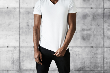 man head: Cropped portrait of attractive African American man in trendy black jeans and white copy space T-shirt for your advertisement. Fit young black male posing against gray brick wall background