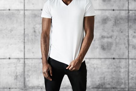 viso uomo: ritratto ritagliata di uomo attraente dell'afroamericano in moda jeans neri e copia spazio bianco T-shirt per la vostra pubblicità. Fit giovane maschio nero posa contro sfondo grigio muro di mattoni