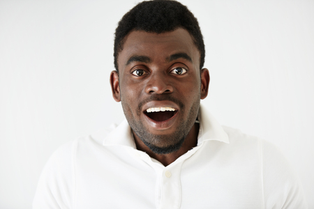 stunned: Closeup portrait of happy young handsome African American man looking excited and stunned with mouth wide open, isolated on white background. Positive human emotions, facial expressions and feelings