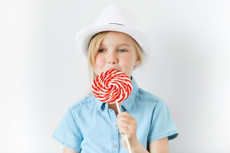 provocative food: Isolated headshot of happy little female child with green eyes and blonde hair wearing white hat and denim shirt, posing with spiral lollipop in her hands, spending nice time with her parents indoor