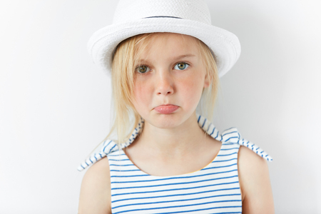 eyes downcast: Portrait of beautiful little girl looking at the camera with sad and disappointed expression. Upset Caucasian 5-year old girl wearing stylish clothes against white background. Human face expressions
