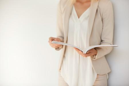 Student meisje draagt ??witte overhemd en beige pak de voorbereiding op het eindexamen aan de universiteit. Aantrekkelijke blonde vrouwelijke ondernemer te lezen van een tijdschrift van vrouwen, terwijl ontspannen in cafe na werkdag Stockfoto - 57650392