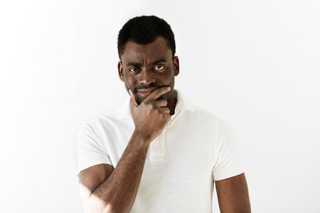 Sceptische jonge zwarte man kijkt naar de camera met verdachte of geërgerd meningsuiting. Voorzichtige en doordachte Afrikaanse mannelijke denken met de handen op zijn kin. Menselijke emoties en gezichtsuitdrukkingen