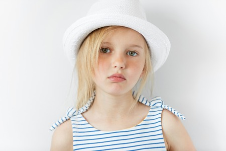 Image of beautiful 5-year female kid wearing stylish clothes looking with serious expression at the camera. Lifestyle and people concept. Adorable Caucasian little girl with green eyes and blonde hair