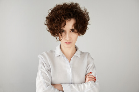 angry hand: Angry businesswoman with brown curly hair looking at camera with sceptical and displeased expression, arms crossed. Portrait of beautiful female boss disappointed or angry with her office workers Stock Photo