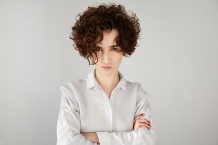 jefe enojado: Empresaria enojada con el pelo rizado marrón que mira a la cámara con expresión escéptica y enojado, con los brazos cruzados. Retrato de la hermosa mujer jefe decepcionado o enfadado con sus trabajadores de oficina Foto de archivo