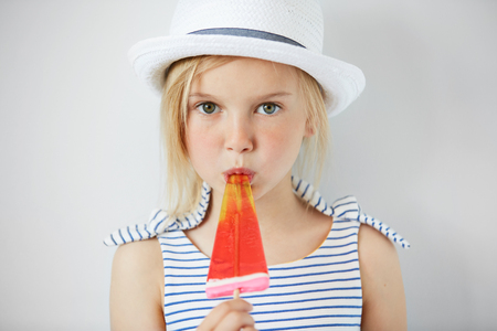 Isolated shot of cute little girl with green eyes and blonde hair, wearing white hat and striped dress, holding fruit ice cream. Portrait of Caucasian child licking popsicle and looking at the camera