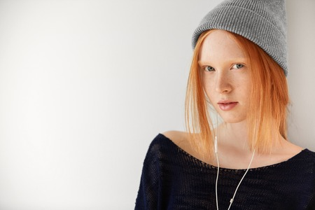 ginger hair: Portrait of redhead young woman with ginger hair and blue eyes wearing hipster cap looking and smiling at the camera while enjoying music posing against white copy space wall for your advertisement Stock Photo