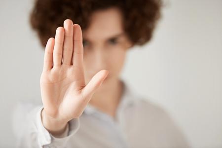 Gros plan tir isolé d'une femme aux cheveux courts et bruns faisant un geste d'arrêt avec sa main. Entreprise féminine montrant un signe d'arrêt, ne voulant pas poursuivre les négociations commerciales. Mise au point sélective sur la main Banque d'images - 57650508
