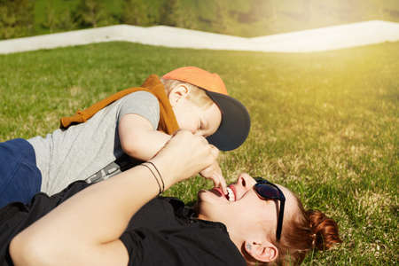 hapiness: Blonde baby boy having fun with his redhead mother in sunglasses, sitting on her and playing with her face. Beautiful young female and son playing in the park on sunny day. Love and hapiness concept.