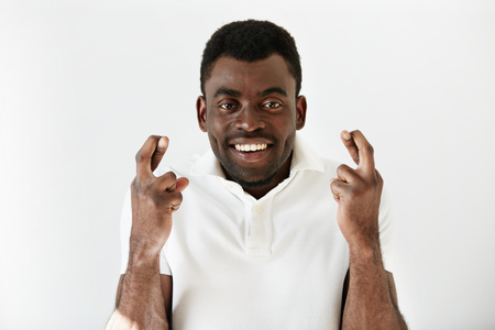 crossing fingers: Close up shot of African man crossing fingers wishing and praying for miracle, hoping for the best, isolated against white copy space wall. Positive human emotions, expressions, feelings adnd attitude Stock Photo
