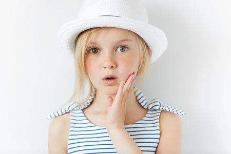 Portret van verrast of bang meisje kijken naar de camera met een hand op haar wang. Sluit omhoog geschoten van blonde Kaukasisch meisje met doen schrikken of geschokte uitdrukking tegen witte studiomuur