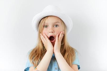 Headshot van mooie verbaasde meisje draagt witte hoed en denim shirt met de handen op de wangen te kijken naar de camera met verbaasde of geschokte uitdrukking, mond wijd open. Human gezichtsuitdrukkingen