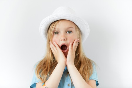 Headshot of pretty surprised little girl wearing white hat and denim shirt with hands on cheeks looking at the camera with astonished or shocked expression, mouth wide open. Human facial expressions