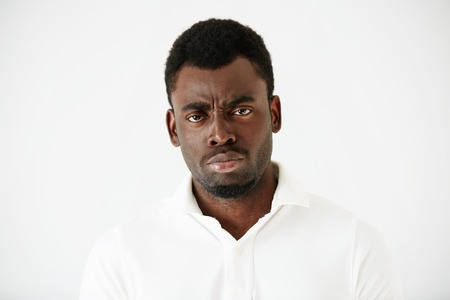 face off: Close up shot of angry, grumpy or pissed off African American man with bad mood, looking and frowning at the camera, posing against white studio wall. Negative human face expressions and body language Stock Photo