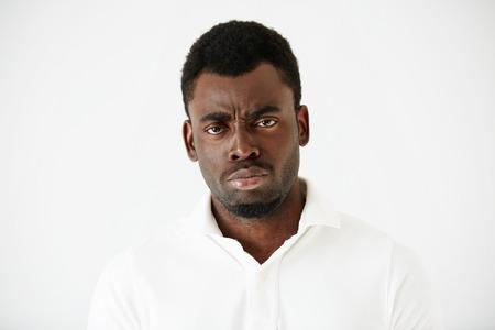 garcon africain: Gros plan de la colère, grincheux ou énervé homme afro-américain avec mauvaise humeur, regarder et fronçant les sourcils à la caméra, ce qui pose contre le mur blanc du studio. Négatif expressions de visage humain et le langage corporel