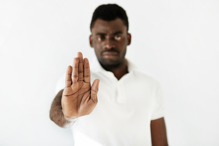 disapproval: Close up portrait of young African man wearing white shirt, looking at the camera in disgust or disapproval on his face, showing stop sign with his palm against white wall. Body language. Selective focus