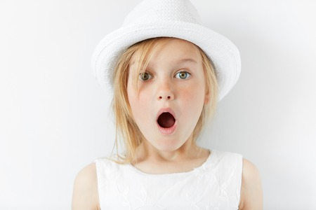 Portrait of emotional beautiful blonde little girl wearing trendy white clothes. Adorable surprised preschool child looking at the camera in astonishment with mouth wide open. shocked with something