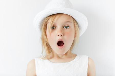 Portret van emotioneel mooi blondemeisje die in witte kleren dragen. Aanbiddelijk verrast peuterkind die de camera in verbazing met wijd open mond bekijken. geschrokken van iets Stockfoto