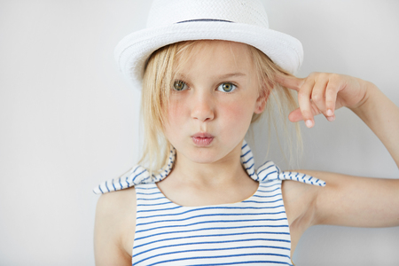 annoyed girl: Close up shot of  annoyed and angry girl wearing white hat and striped dress, holding index finger at her head with are you crazy gesture. Isolated portrait of little Caucasian 5-year old child