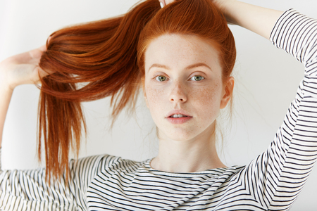 ginger hair: Youth and happiness concept. Close up view of beautiful Caucasian teenage girl in sailor shirt, looking at the camera, playing with her long ginger hair. Young woman with perfect healthy freckled skin Stock Photo
