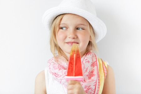 contended: Smiling child with popsicle cunningly looking sideways indoors. Positive emotions, contended look and summer careless atmosphere makes kid look nice and shinny.