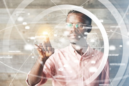 pointing device: Portrait of African man in glasses, using digital device, pointing at icons on futuristic screen interface against high-tech interior, looking with serious concentrated expression. Selective focus