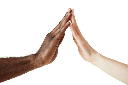Interraciale vriendschap en samenwerking concept. Twee mensen od verschillende etnische groepen hand in hand in de eenheid, respect en begrip. Vrede en eenheid tegen racisme. Blanke vrouw en zwarte man handen Stockfoto