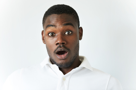 Close up of amazed young African American man in white polo shirt, having fun indoor, looking at the camera with excited expression, astonished with sale prices. Human face expressions and emotions