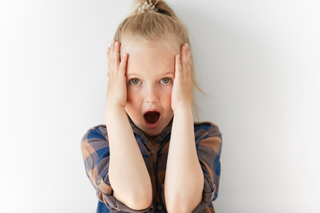 horrified: Blond scared child looking at camera holding head with her hands. She is gaping, her eyes are wide-open. Little girl is amazed and horrified by unexpected news.