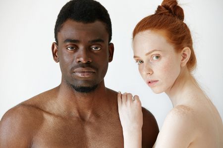 naked african: Pure unconditional love: beautiful Caucasian young woman with red hair and freckles embracing her naked African boyfriend or husband, both looking at the camera. Interracial relationships concept