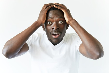 Portrait of shocked young African American man wearing white blank T-shirt looking at the camera in surprise, stunned with some incredible story, holding hands on head. Human expressions and emotions