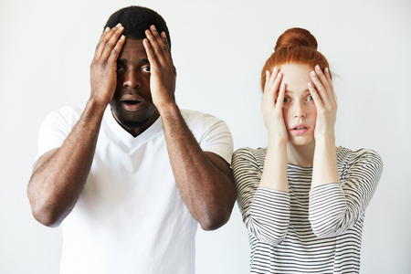 wall covering: Portrait of shocked interracial couple: African man and redhead Caucasian woman standing together against white wall, covering face, looking at the camera with scared and disappointed expression