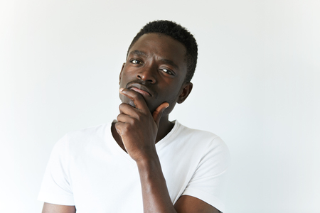 indecisive: Handsome African man in white T-shirt, looking at the camera with thoughtful skeptical expression, holding hand on his chin. Black male with mistrustful look posing against white concrete wall Stock Photo