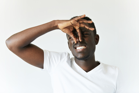 intolerable: Close up shot of African man in casual clothes pinching his nose to avoid bad smell. Dark-skinned student looking at the camera with disgusted expression while something is stinking. Body language