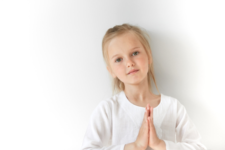 Portrait of angel-like European child joining her hand like a prayer with tilted head. Shinny and pure atmosphere make girl look pure and balanced like a yogi in mediation.