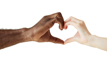 interracial love: Two people of different races and ethnicities holding hands in the shape of a heart, symbolizing love, peace and unity. African man and Caucasian woman holding hands together. Interracial love concept
