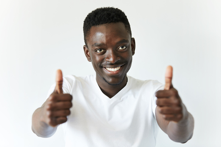 thumbsup: Selective focus. Portrait of black employee or customer with ultrawhite smile, looking at the camera with happy expression, showing thumbs-up with both hands, achieving career goals. Body language