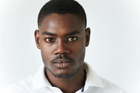 Zeer gedetailleerde close-up portret van knappe jonge Afro-Amerikaanse man die modieuze polo shirt, kijkend naar de camera met seus doordachte meningsuiting. Menselijk gezicht expressie en emoties Stockfoto