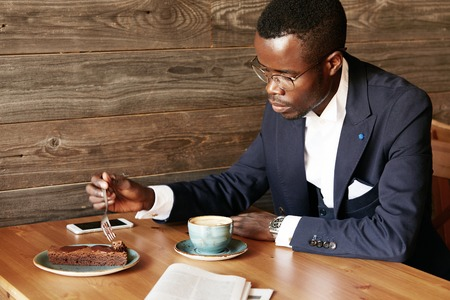 hard day at the office: African corporate worker in formal suit and spectacles eating cake and drinking coffee after hard working day in the office, sitting at his favorite caf?, using cell phone with blank cope space screen Stock Photo
