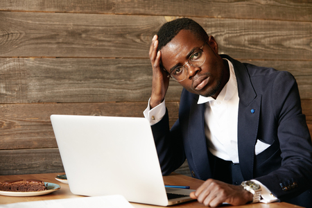 distant work: Portrait of handsome African banker using laptop for distant work while sitting at the cafe, having coffee during lunch break, looking at the camera with serious expression, resting elbow on the table