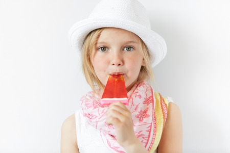 sucking lollipop: Cute blond girl in summer hat and nice scarf sucking lollipop looking at camera on white background. Tiny kid looks obedient and enjoying her sweet yummy ice pop.