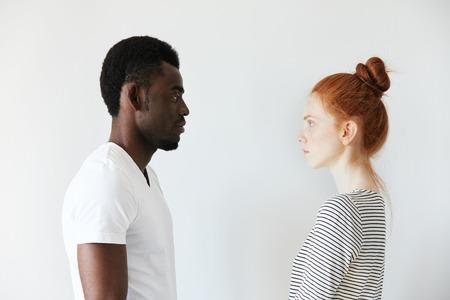 カップル見てお互い目の前に白い背景の上の横の肖像画。アフロ男立っているまだ、白人の赤毛の女の子同様夫を妻のように深刻な表情で彼を見て 写真素材