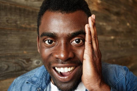 blown away: Close up portrait of happy handsome young black man looking in excitement at the camera, holding hands on cheeks with mouth wide open against wooden wall. Positive human emotions and facial expression