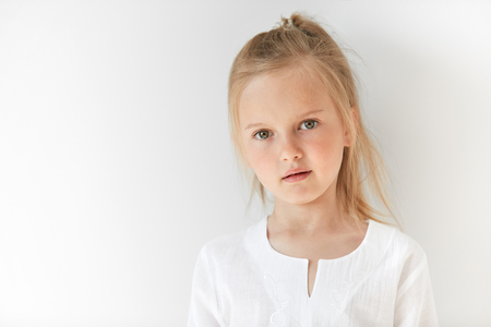 restful: Little blond girl with attractive appearance posing in white background. Natural beauty and morning light suit her pretty and restful facial expression.