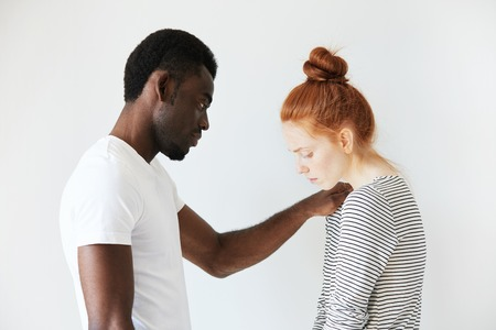 sympathize: A touching scene of African American man comforting young redhead girl. He put his arm on her shoulder to sympathize her failure and to support her in hard times. Caucasian girl looks down in sorrow.